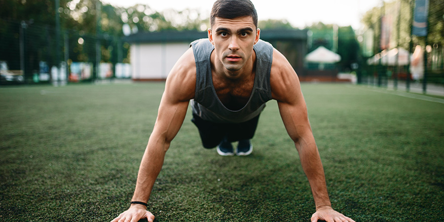 Athlete doing push up exercise outdoors. Buy cbd for athletes online. CBD for pain management.