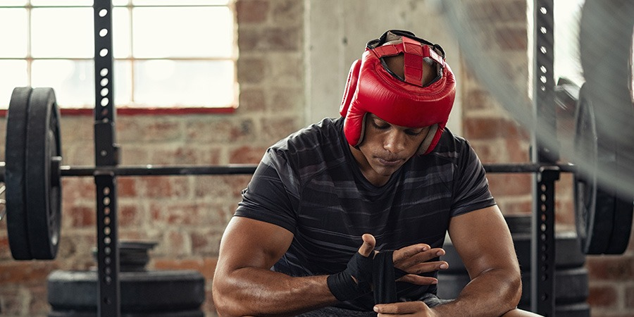 Boxer man wrapping his hands with gloves. Buy CBD online. best cbd products for athletes. cbd oil for muscle recovery.
