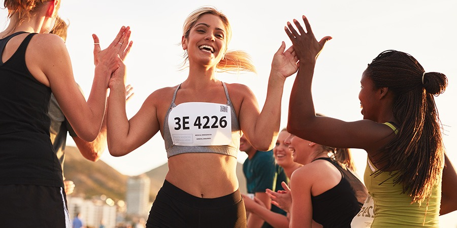 Sportswoman giving high five to her team. How to use cbd for athlete recovery. cbd cream for athletes. best cbd cream for athletes.