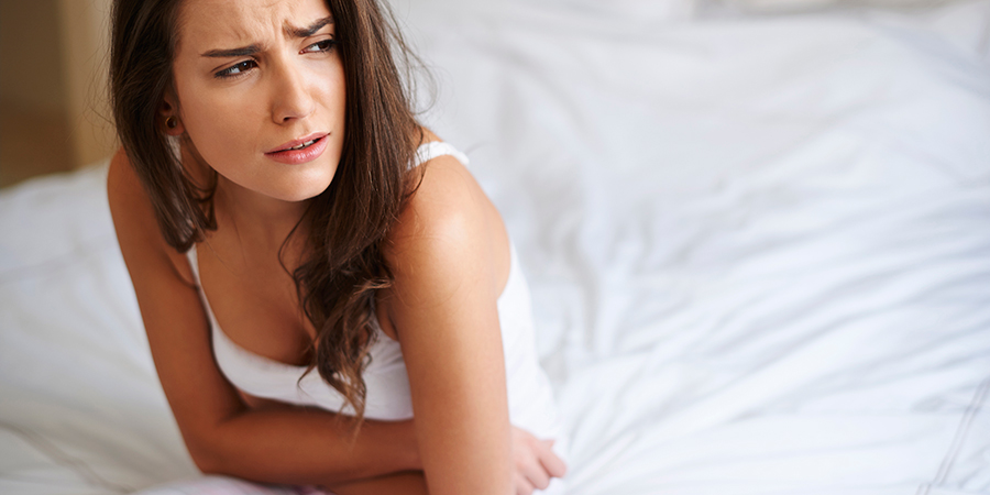 woman with PMS cramps. cbd oil for heavy periods.