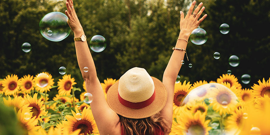 Woman with arms up surrounded by sunflowers.